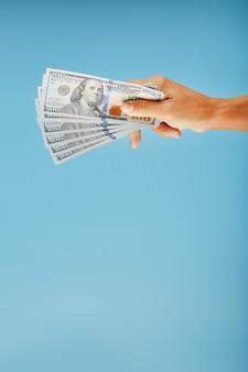 Pakje bankbiljetten ter beschikking op een blauwe achtergrond. het concept van financiële bijstand.