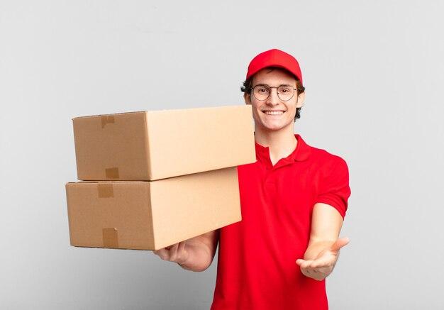 Pakket bezorg jongen vrolijk glimlachend met vriendelijke, zelfverzekerde, positieve blik, aanbieden en tonen van een object of concept