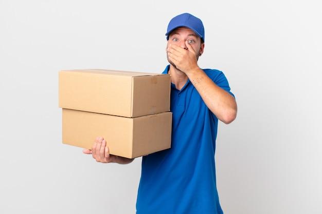 Pakket bezorg man die mond bedekt met handen met een geschokte