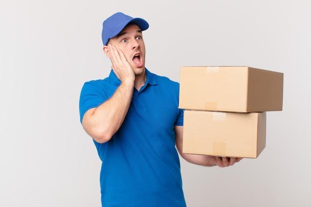 Pakket bezorg man die zich gelukkig, opgewonden en verrast voelt, opzij kijkend met beide handen op het gezicht