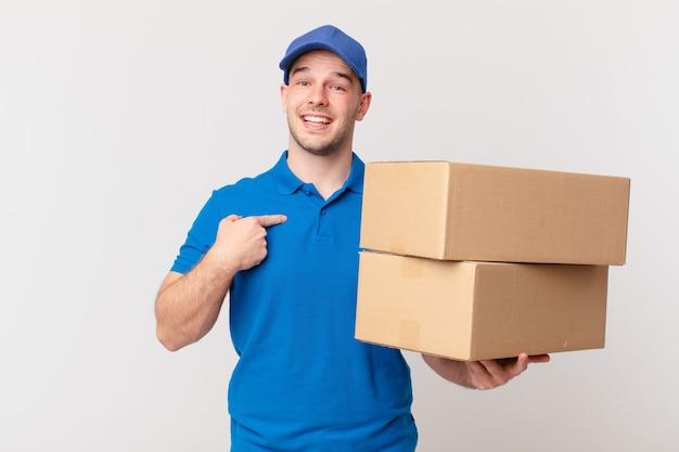 Pakket bezorgt de man die zich gelukkig, verrast en trots voelt, wijzend naar zichzelf met een opgewonden, verbaasde blik