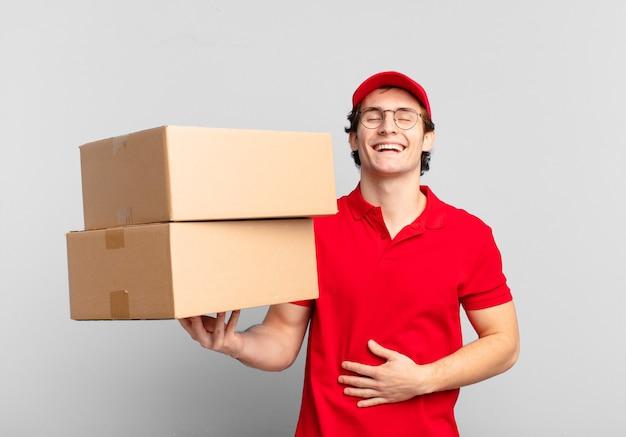 Pakket bezorgt jongen die hardop lacht om een hilarische grap, zich gelukkig en opgewekt voelt, plezier heeft