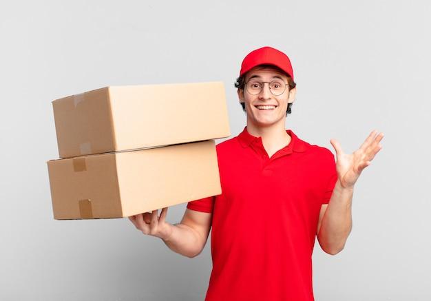 Pakket bezorgt jongen die zich blij, verrast en opgewekt voelt, lacht met een positieve houding, een oplossing of idee realiseert