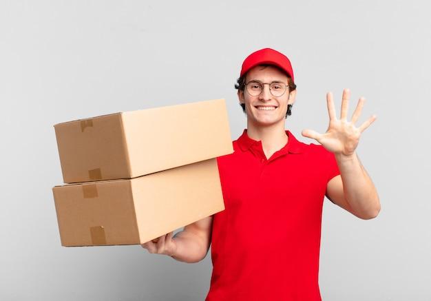 Pakket bezorgt jongen glimlachend en vriendelijk, met nummer vijf of vijfde met hand naar voren, aftellend