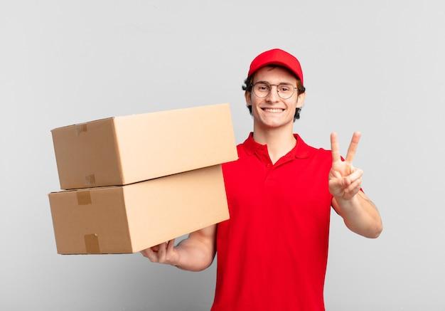 Pakket bezorgt jongen glimlachend en ziet er gelukkig, zorgeloos en positief uit, gebaart overwinning of vrede met één hand