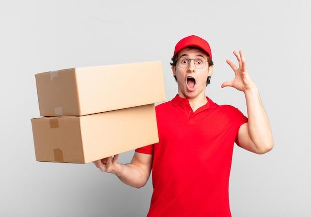 Pakket bezorgt jongen schreeuwend met handen in de lucht, woedend, gefrustreerd, gestrest en overstuur