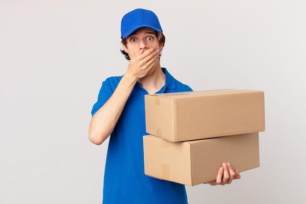 Pakket bezorgt man die mond bedekt met handen met een geschokte