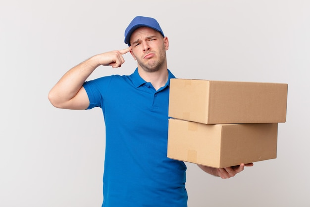 Pakket bezorgt man die zich verward en verbaasd voelt en laat zien dat je gek, gek of gek bent