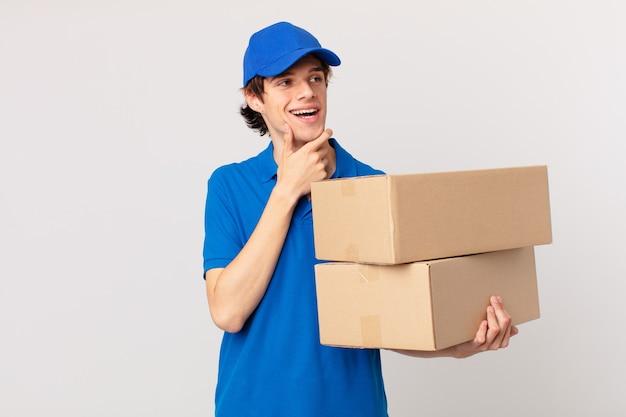 Pakket bezorgt man glimlachend met een gelukkige, zelfverzekerde uitdrukking met de hand op de kin