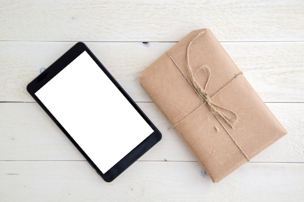 Pakket, cadeau verpakt in milieuvriendelijk papier en tablet op lichte houten achtergrond. het uitzicht vanaf de top