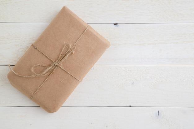 Pakket, cadeau verpakt in milieuvriendelijk papier op lichte houten achtergrond. het uitzicht vanaf de top