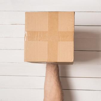 Pakket in mannelijke handen. bovenaanzicht. witte tafel op de achtergrond