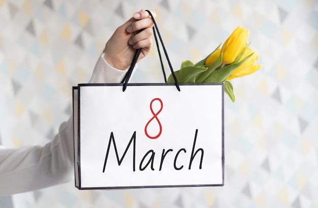 Pakket met bloemen in de hand voor vrouwendag op 8 maart met het nummer en de maand.