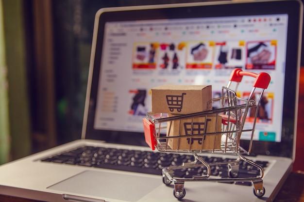 Pakket- of papierdozen met een winkelwagenlogo in een trolley op een laptop toetsenbord