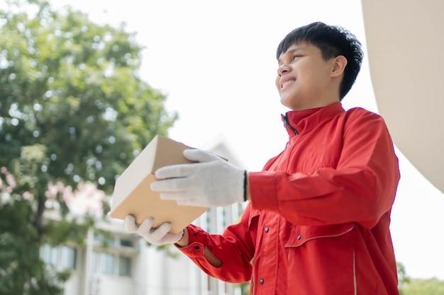 Pakketbezorgingsconcept de postbode draagt een rood uniform en handschoenen van sommige logistieke bedrijven die het pakket aan een klant overhandigen tijdens de covid19-pandemie.