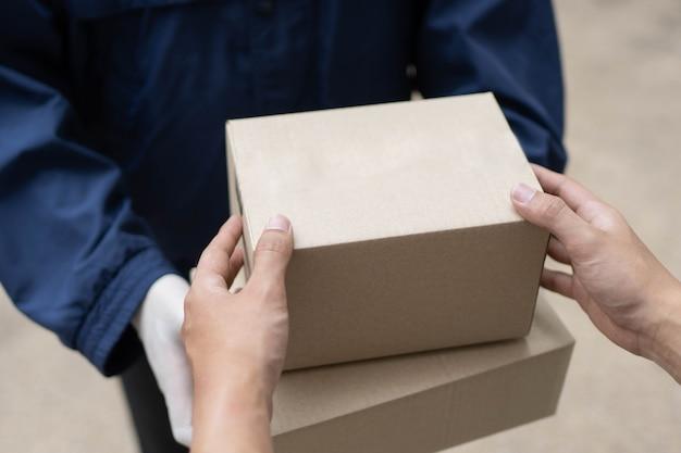 Pakketbezorgingsconcept de postbode in witte rubberen handschoenen en lichtgewicht donkerblauwe jas die twee kleine pakketposten overhandigt aan zijn cliënt.