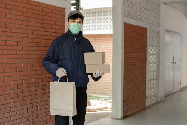 Pakketbezorgingsconcept de staande postbode die een lichtgrijze pet draagt met een zak aan de linkerhand en twee dozen aan de rechterhand en klaar om deze spullen naar zijn klanten te brengen.