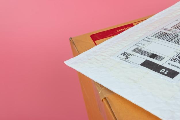 Pakketdozen worden verzonden door rederijen op een felroze achtergrond.