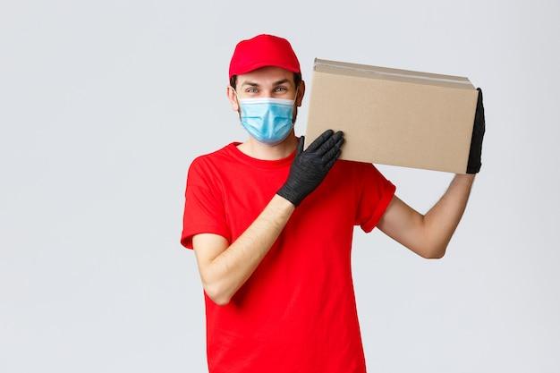 Pakketten en pakketbezorging, covid-19 quarantainebezorging, overboekingsopdrachten. vriendelijke koerier brengt de bestelling naar het huis van de klant, houdt de pakketdoos op de schouder, draagt een gezichtsmasker en rubberen handschoenen