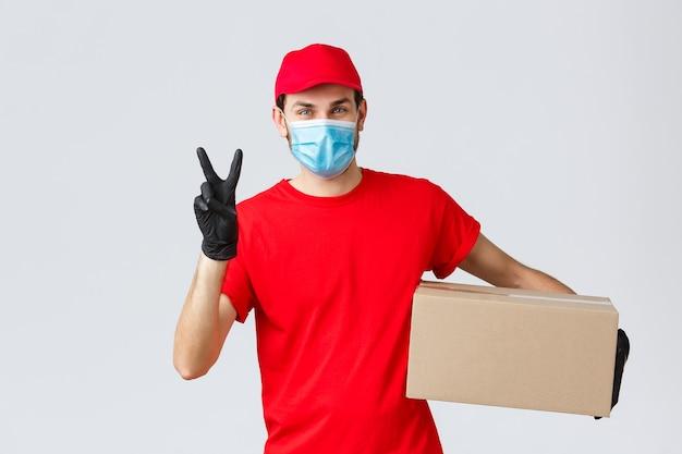 Pakketten en pakketbezorging, covid-19 quarantainebezorging, overboekingsopdrachten. vriendelijke koerier in rood uniform, gezichtsmasker en handschoenen, bezorg bestelling aan klant, houd doos vast, toon vredesteken