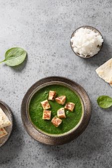 Palak paneer gemaakt van spinazie en paneer kaas op grijze steen achtergrond indiase keuken