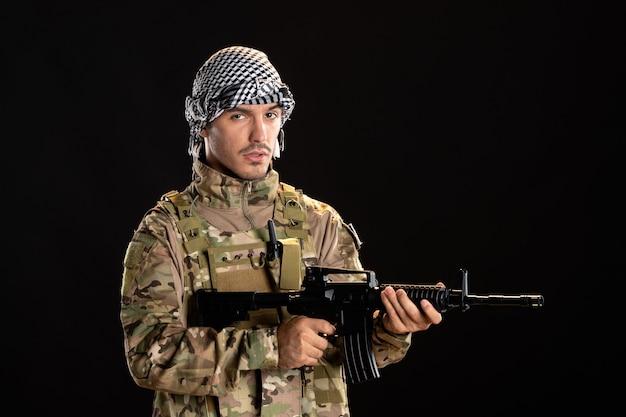 Palestijnse soldaat in camouflage met machinegeweer op zwarte oppervlakte palestijnse tankoorlog
