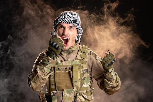 Palestijnse soldaat schreeuwt door radioset op donkere muur