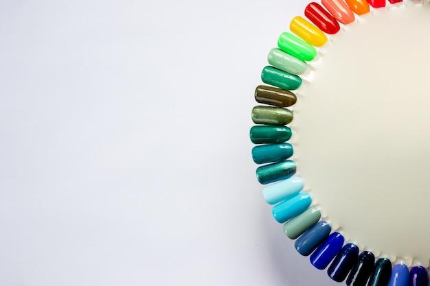 Palet met kleurstalen van nagellak geïsoleerd op een witte achtergrond. verschillende felle kleuren. reclame voor kleurrijke nagellak manicure stalen. bovenaanzicht van nail art wielpalet. kopieer ruimte