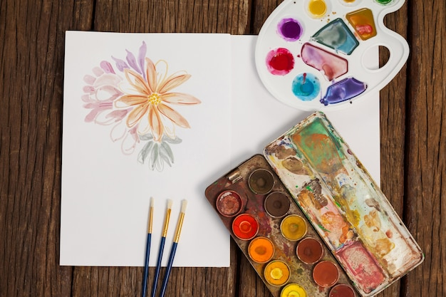 Palet, penselen en wit blad op houten tafel