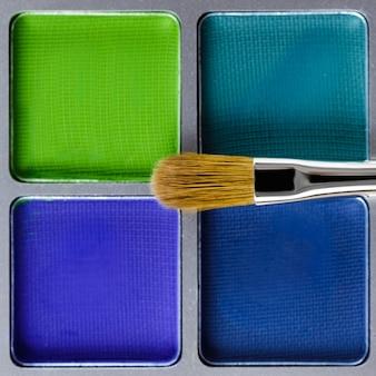 Palet van blauwe en groene oogschaduw en make-up borstel
