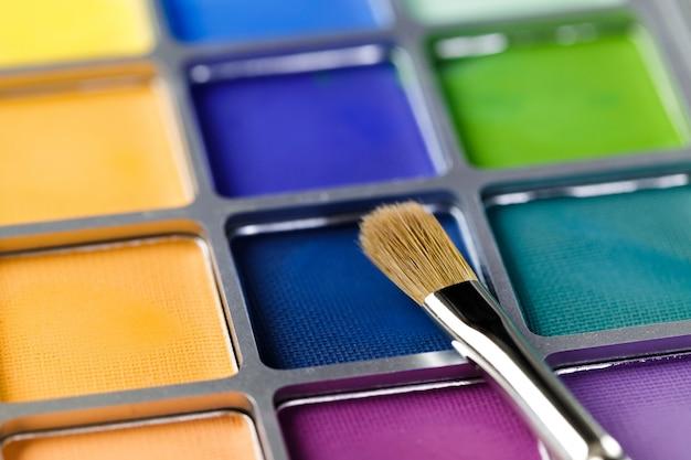 Palet van blauwe, groene en gele oogschaduw en make-up kwast
