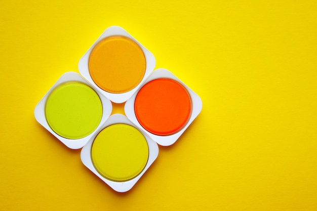 Palet van gele en oranje tinten aquarelverf op geel