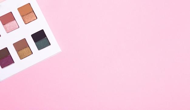 Palet van heldere schaduwen op roze achtergrond close-up en kopieer de ruimte