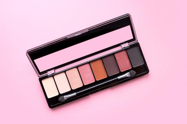 Palet van oogschaduw in bruine tinten, mat en flikkering oogschaduw op een roze achtergrond, bovenaanzicht, kopie ruimte. herfst, lente-oogschaduwpalet met 8 kleuren, beige, rood, bruin, zwart