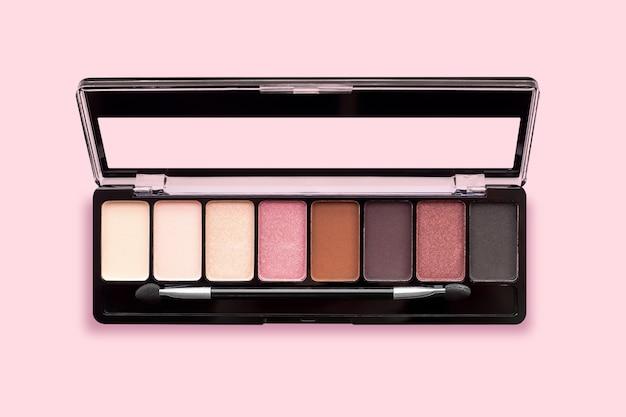 Palet van oogschaduw in bruine tinten, mat en shimmer oogschaduw op een roze achtergrond, bovenaanzicht. herfst oogschaduwpalet met 8 kleuren, beige, rood, bruin, zwart