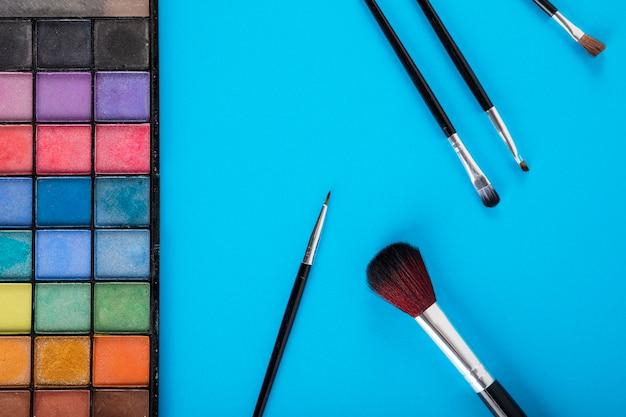 Palet van poederkleuren en borstels op blauwe achtergrond