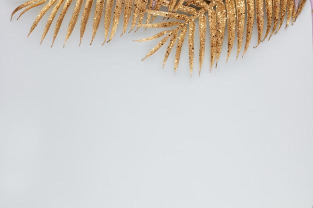 Palm bladgoud op blauw. palmblad, plat leggen en bovenaanzicht.