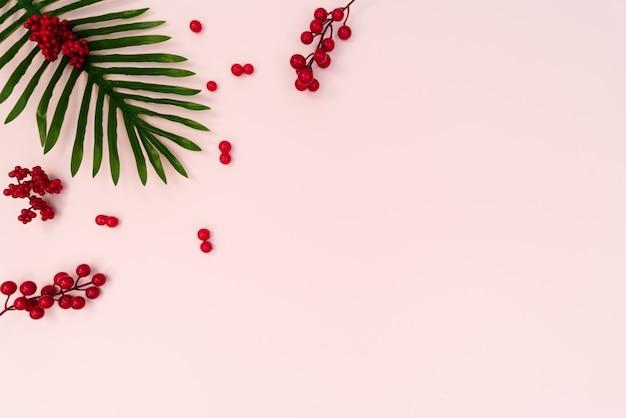 Palm met rode kers op roze achtergrond. plat lag, bovenaanzicht