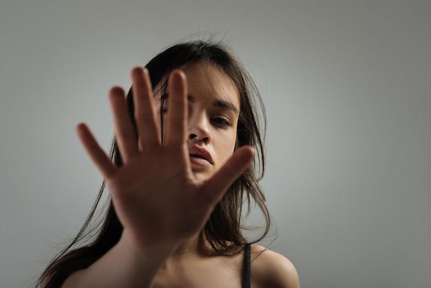 Palm. vrij humorloze donkerharige jonge vrouw die staart en lang haar heeft en haar gezicht met haar handpalm sluit