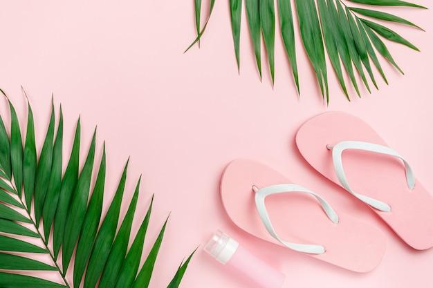 Palmblad, slippers en zonnebrandcrème fles op pastel roze achtergrond. kopieer de ruimte direct boven.