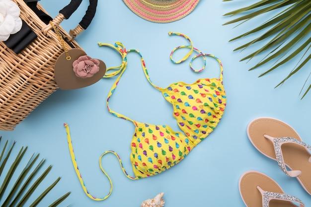 Palmbladeren, modieuze hoed, bikini, slippers, stro-strandtas op een licht pastelblauw oppervlak, reis- en vakantieconcept, bovenaanzicht