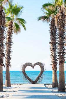 Palmbomen en hart vlakbij de zee. zomer concept