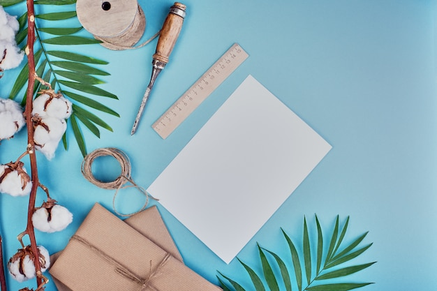 Palmtak, geschenkdozen en jute touw hank op een blauwe ruimte, zomer stijl. vrije ruimte voor tekst. plat liggen. kopieer ruimte.