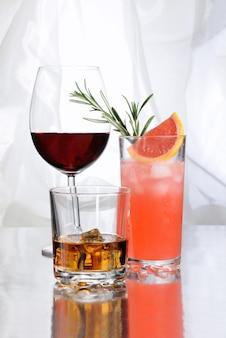 Paloma cocktail whisky in rocks glas met ijsblokjes rode wijn in bordeauxvormig glas