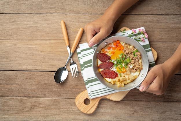 Pan-eieren bestrooid met chinese worst, spekblokjes, ontbijt.