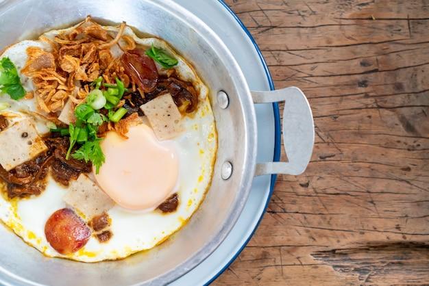 Pan fried egg-topping met thaise worst op houten oppervlak