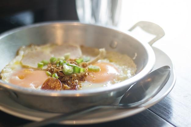 Pan - fried egg with toppings, worsten, koriander en uien bovenop