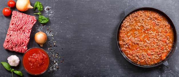 Pan met bolognese saus en ingrediënten om te koken, bovenaanzicht met kopie ruimte