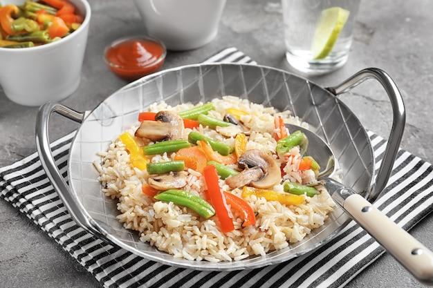 Pan met bruine rijst en groenten op tafel