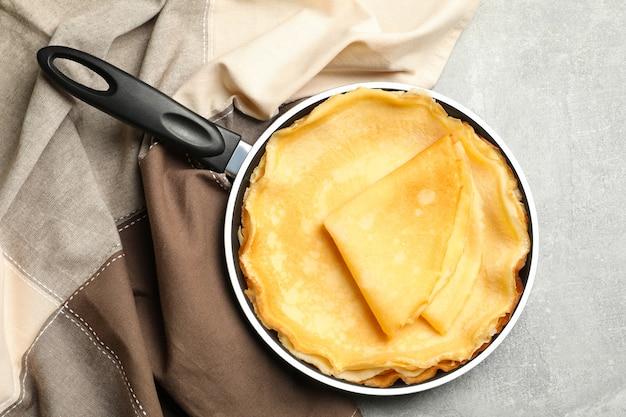 Pan met dunne pannenkoeken en keukenpapier op grijze achtergrond